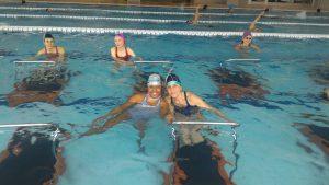 Due amiche si divertono durante un allenamento speciale per il Carnival Party in piscina presso Q-bo Wellness