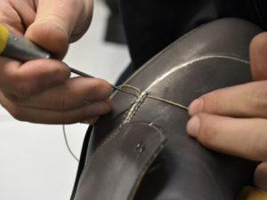 un artigiano lavora ad una calzatura